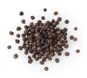 Heap of black pepper corns isolated